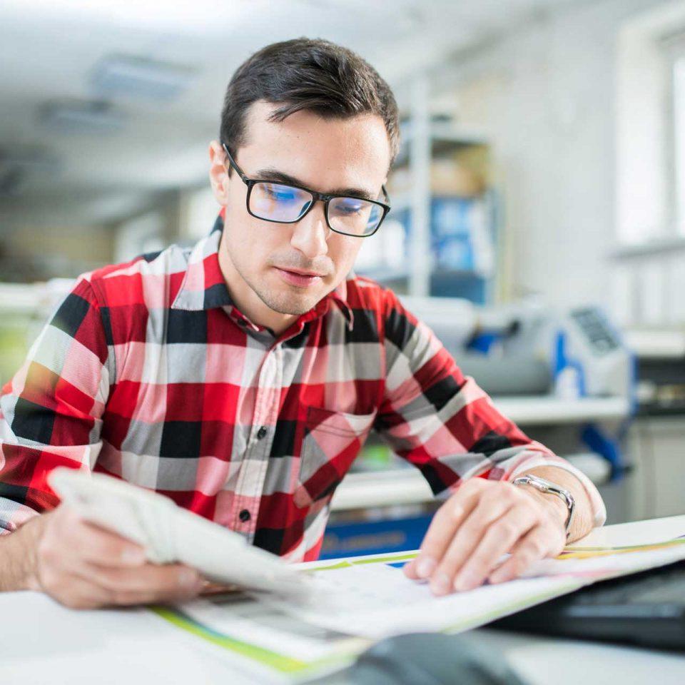 concentrated-designer-examining-quality-of-print-U4NWQDP.jpg